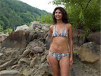 Mature woman in bikini posing by rocks,smiling Stock Photo - Premium Royalty-Freenull, Code: 6106-07023418