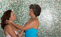 Two women in swimwear looking in eyes against mosaic wall Stock Photo - Premium Royalty-Freenull, Code: 6106-07023957