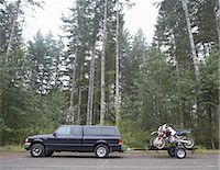 Truck towing motorbikes on trailer in forest, side view Stock Photo - Premium Royalty-Freenull, Code: 6106-07024371