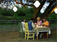 Four friends dining in yard at dusk Stock Photo - Premium Royalty-Freenull, Code: 6106-07024387
