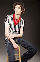 Young man posing on stool Stock Photo - Premium Royalty-Freenull, Code: 6106-07024484