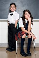 school girl uniforms - School boy (6-7) standing behind sister (12-13) sitting on chair in class, portrait Stock Photo - Premium Royalty-Freenull, Code: 6106-07024630
