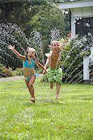 Boy and girl (5-6) jumping through sprinkler in garden Stock Photo - Premium Royalty-Freenull, Code: 6106-07024775