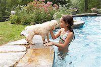 dog kissing girl - Girl (8-9) in swimming pool, kissing dog, side view Stock Photo - Premium Royalty-Freenull, Code: 6106-07024802