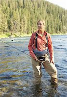 Mid adult woman with fishing rod in middle of river Stock Photo - Premium Royalty-Freenull, Code: 6106-07025484