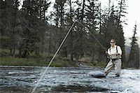Young woman fly-fishing in river Stock Photo - Premium Royalty-Freenull, Code: 6106-07025490