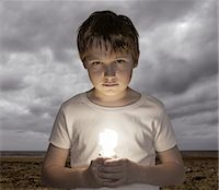 Boy (12-13) holding energy saving bulb on beach, portrait Stock Photo - Premium Royalty-Freenull, Code: 6106-07025849