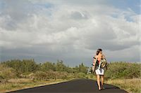 road landscape - Young woman carrying surfboard on country road Stock Photo - Premium Royalty-Freenull, Code: 6106-07026098