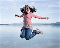 USA, California, San Francisco, Point Pinloe, girl (6-7) jumping near lake Stock Photo - Premium Royalty-Freenull, Code: 6106-07026524