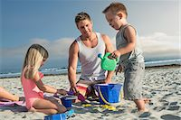 Young man playing with son and daughter on beach Stock Photo - Premium Royalty-Freenull, Code: 614-07031177