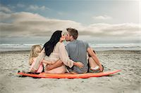 Young family sitting on surfboard on beach with parents kissing Stock Photo - Premium Royalty-Freenull, Code: 614-07031191