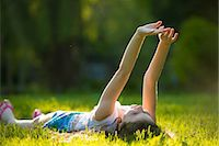 Girl lying on grass with arms raised Stock Photo - Premium Royalty-Freenull, Code: 614-07031233