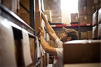 piles of work - Worker reaching up for cardboard box stored in warehouse Stock Photo - Premium Royalty-Freenull, Code: 614-07031311