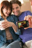 Couple taking self portrait whilst moving house Stock Photo - Premium Royalty-Freenull, Code: 614-07031339