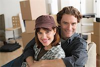 Portrait of couple resting on chair whilst moving home Stock Photo - Premium Royalty-Freenull, Code: 614-07031355