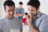 Young male colleagues chatting in office Stock Photo - Premium Royalty-Freenull, Code: 614-07031370