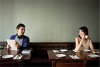 flirting - Young man and young woman smiling at each other in restaurant Stock Photo - Premium Royalty-Freenull, Code: 614-07031499