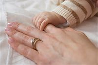 Baby boy holding mother's hand, close up Stock Photo - Premium Royalty-Freenull, Code: 614-07031697