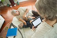 Senior man tickling grandson on rug Stock Photo - Premium Royalty-Freenull, Code: 614-07031721