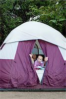 Toddler twins and father peeking out of tent Stock Photo - Premium Royalty-Freenull, Code: 614-07031803