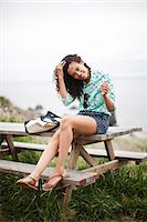 Young woman sitting on picnic table smiling, portrait Stock Photo - Premium Royalty-Freenull, Code: 614-07031929
