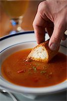 spicy - Hand dipping bread into bowl of tomato soup Stock Photo - Premium Royalty-Freenull, Code: 614-07032102