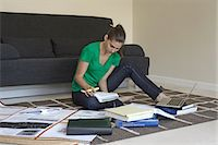 Mid adult woman sitting on floor studying Stock Photo - Premium Royalty-Freenull, Code: 614-07032180