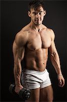 Muscular young man with a dumbbell over black Stock Photo - Royalty-Freenull, Code: 400-07032919