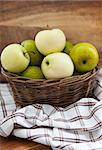 Fresh green and yellow apples in basket on wooden table and wooden background
