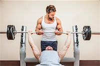 A handsome young muscular sports man doing weight lifting and gets help from his friend Stock Photo - Royalty-Freenull, Code: 400-07050910