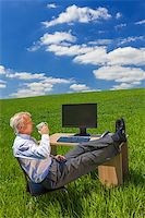 Man or male businessman relaxing feet up at a desk with a computer in a green field drinking tea or coffee Stock Photo - Royalty-Freenull, Code: 400-07055355