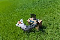 Business aerial high angle concept shot showing an older male man or businessman relaxing feet up at a desk with a computer in a green field Stock Photo - Royalty-Freenull, Code: 400-07055356