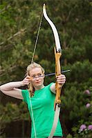 Concentrating blonde woman practicing archery in the countryside Stock Photo - Royalty-Freenull, Code: 400-07058557