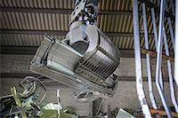 Excavator lifting scrap metal in warehouse Stock Photo - Premium Royalty-Freenull, Code: 649-07063371