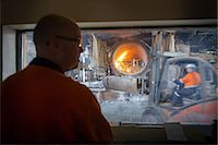 Controller watching furnace at aluminum recycling plant Stock Photo - Premium Royalty-Free, Artist: Cultura RM, Code: 649-07063382