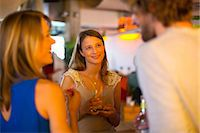 Friends enjoying drinks together in bar Stock Photo - Premium Royalty-Freenull, Code: 649-07063517