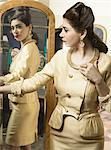 Woman in vintage clothes looking in mirror