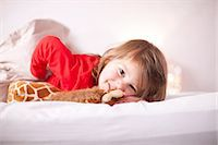 Young girl lying on bed with toy giraffe Stock Photo - Premium Royalty-Freenull, Code: 649-07063622