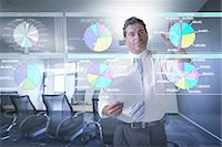Businessman looking at pie charts on interactive screen Stock Photo - Premium Royalty-Freenull, Code: 649-07063662