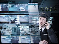 Security guard monitoring camera visuals on interactive screen Stock Photo - Premium Royalty-Freenull, Code: 649-07063668