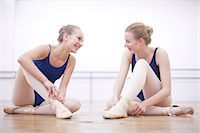 Two ballerinas chatting whist fastening ballet slippers Stock Photo - Premium Royalty-Freenull, Code: 649-07063706