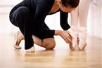 Teacher adjusting foot position of ballerina Stock Photo - Premium Royalty-Freenull, Code: 649-07063727