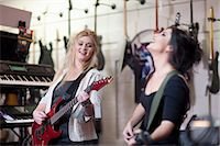 Two young women trying electric guitars in music store Stock Photo - Premium Royalty-Freenull, Code: 649-07063812