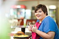 Young woman in cafe with unhealthy meal Stock Photo - Premium Royalty-Freenull, Code: 649-07064043