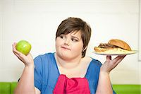 fat lady sitting - Young woman choosing between an apple and a burger Stock Photo - Premium Royalty-Freenull, Code: 649-07064044