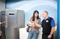 fridge - Woman negotiating with salesman in showroom Stock Photo - Premium Royalty-Freenull, Code: 649-07064060