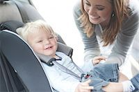 Mother checking baby son in back seat of car Stock Photo - Premium Royalty-Freenull, Code: 649-07064197