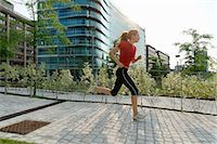 Young woman running past office buildings Stock Photo - Premium Royalty-Freenull, Code: 649-07064318