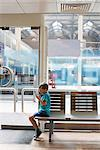 Young boy in train station waiting room playing electronic game