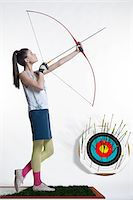 Side view of young, woman archer, aiming bow and arrow, studio shot on white background Stock Photo - Premium Royalty-Freenull, Code: 600-07066926